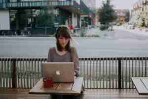 woman working remotely sitting outside with computer