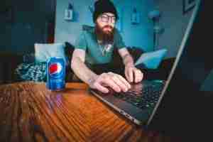 man wearing black hat working on laptop with can of pepsi sitting next to him