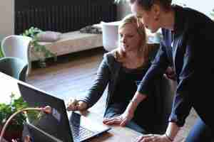 two women consulting in front of a laptop